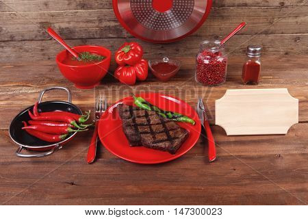 red theme lunch: fresh grilled bbq roast beef steak red plate green chili tomato soup ketchup sauce paprika jug glass pepper american peppercorn modern cutlery served wooden table with empty nameplate