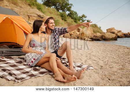 Young handsome man pointing at something while sitting with girlfriend at the tent on the beach