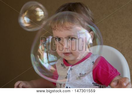 child inflates soap bubbles sitting on a chair in the room