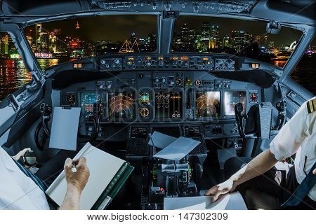 Cockpit and board of an airplane in Sydney skyline at night with pilots arms and blank white papers for copy space