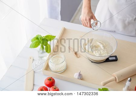 Woman Adding Water To Flour In A Bowl.