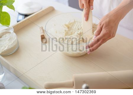 Woman Mixing Pizza Dough With Wooden Spatula.