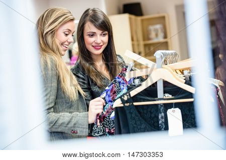 Women selecting a dress while shopping for clothes in apparel shop