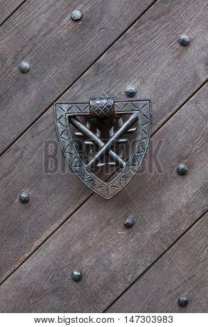 Doorknocker on the wooden gate fixed with rivets in Kokorin Castle in Central Bohemia, Czech Republic.