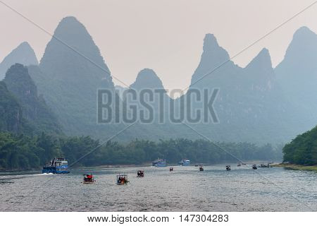 Xingping China - October 20 2013: A tourist boats travels the magnificent scenic route along the Li river from Guilin to Yangshuo in the haze.