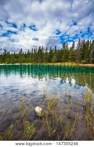 Jasper National Park, lake Annette, Canadian Rocky Mountains.  The picturesque oval lake with clear water