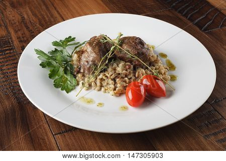 Veal (beef) cheeks with pearl barley porridge and greens in a white plate. Wooden background.