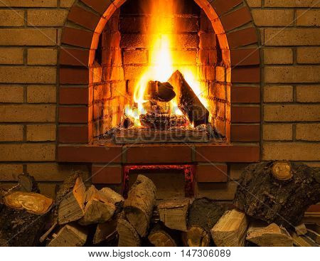 Pile Of Firewood And Tongues Of Fire In Fireplace