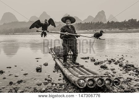 Yangshuo China - October 20 2013: Cormorant fisherman with ancient bamboo boat on the Li River in Yangshuo Guangxi China. Black and white photography (sepia).