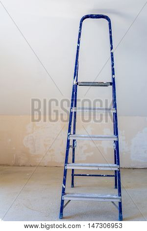 Blue dirty stepladder at plaster wall background