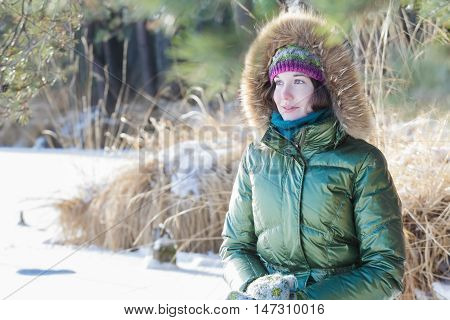 Young woman wearing green hooded real fur trim down coat is enjoying view in winter forest outdoors