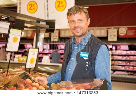 Market Assistant Holding Box Of Fruits In The Supermarket