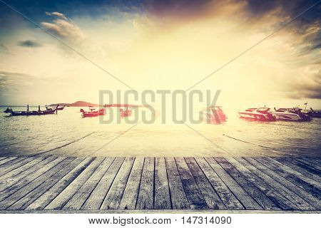 View from wooden pier with many boat during sunset