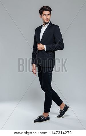 Full length of an serious young man in black suit posing over grey background