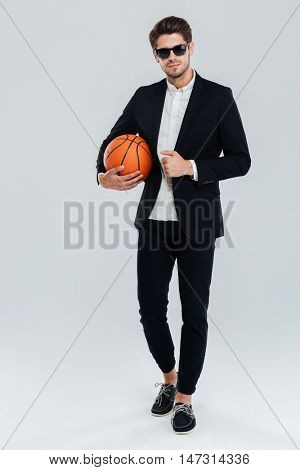 Full length portrait of a confident handsome man in sunglasses and black suit holding basket ball over grey background