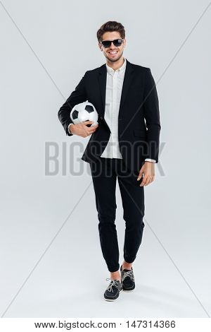 Full length portrait of a smiling handsome man in sunglasses and black suit holding soccer ball over grey background