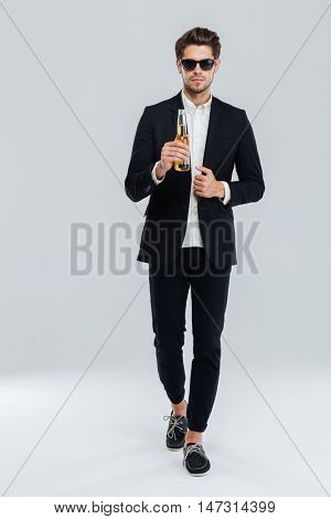 Full length portrait of a handsome young man in black suit and sunglasses walking and holding beer bottle over grey background