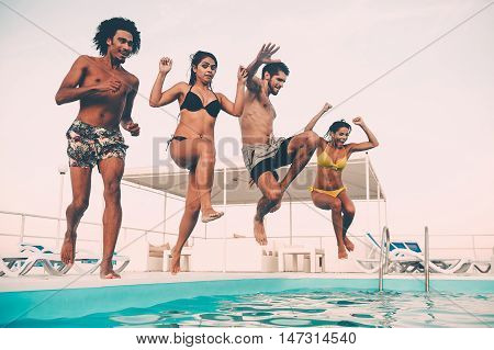 Time to get refreshed. Group of beautiful young people looking happy while jumping into the swimming pool together