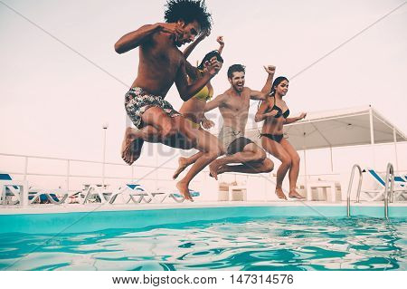 Summer pool party. Group of beautiful young people looking happy while jumping into the swimming pool together