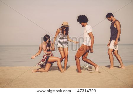 Beach ball with friends. Group of cheerful young people playing with soccer ball on the beach with sea in the background