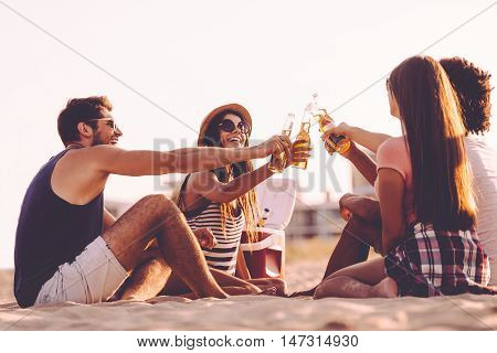 Cheers! Cheerful young people toasting with beer bottles while enjoying picnic on the beach