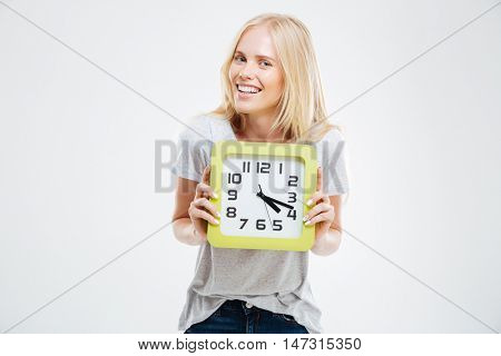 Portrait of a smiling woman holding wall clock isolated on a white background