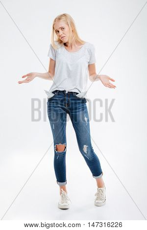Stressed young woman showing empty pockets isolated on a white background