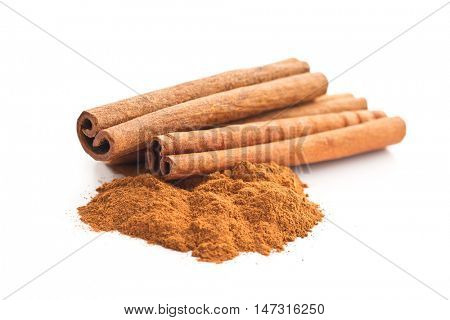 Cinnamon sticks and ground cinnamon isolated on white background.