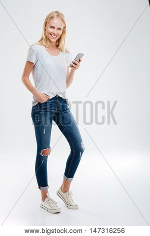 Full length portrait of a happy young blonde woman holding mobile phone and looking at camera isolated on a white background