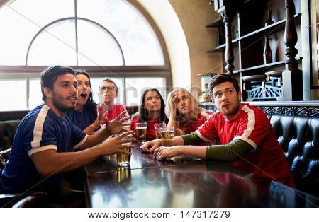 people, leisure and sport concept - worried friends or football fans drinking beer and watching soccer game or match at bar or pub, supporting two teams with different shirt color