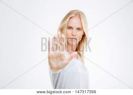 Portrait of a beautiful girl showing stop sign with palm isolated on a white background