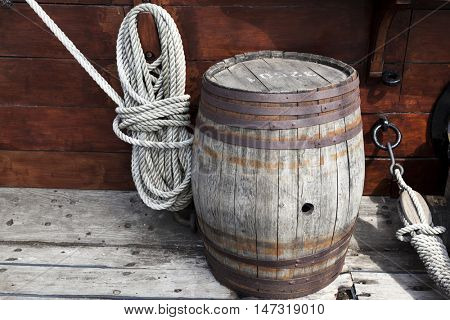 Older intricate marine ropes and old wooden barrel on deck of a ship.
