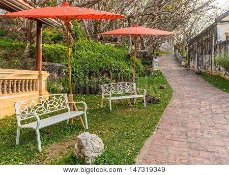 Bench under red umbrella in the park.