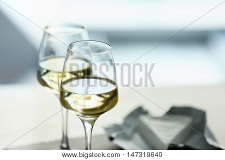 Glasses with white wine and cheese on a table