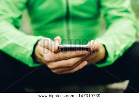 closeup of a young caucasian sportsman wearing sport clothes using his smartphone outdoors