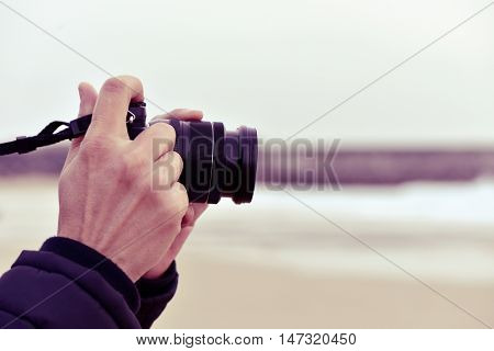 closeup of a young caucasian man taking a picture in front of the sea