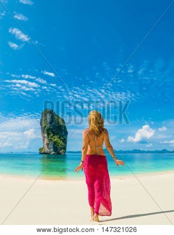 Woman  with sarong walking on the beach in Poda Thailand