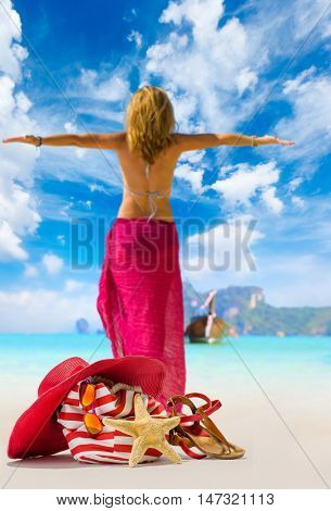 view of a womanstanding on the beach  with straw hat and beach bag - focused on the bag