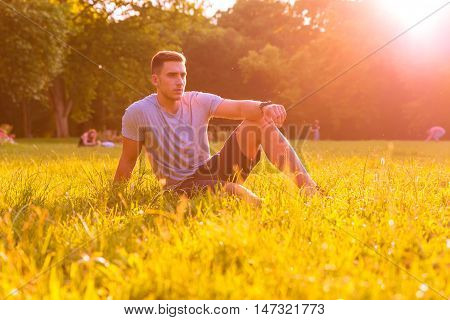 A handsome young man relaxing in the sunset and sitting in the grass.