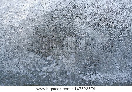 Textured background of bizarre frozen ice on glass in winter