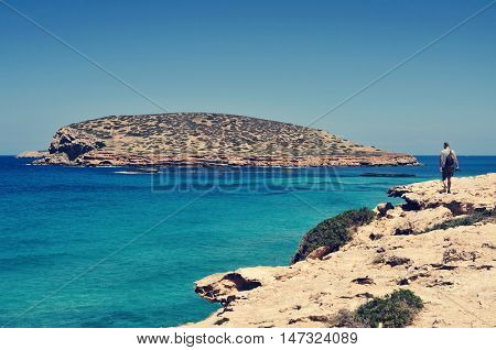 a young tourist man with a camera in his hand walks next to the Mediterranean sea facing the Illa des Bosc island, in Ibiza island, Spain