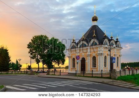 RYBINSK RUSSIA - JULY 21 2016: Unidentified people are relaxing near Chapel Nicholas the Miracle Worker on waterfront at sunset Rybinsk Russia