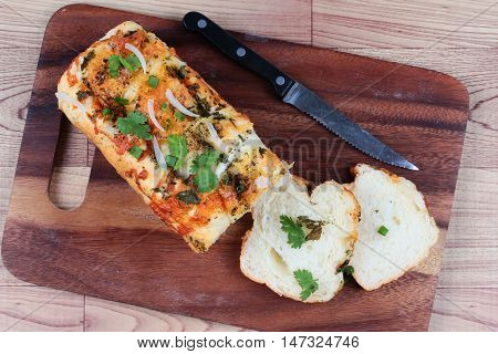 Spinach bread with knife on butcher served.