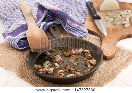 chrispy roasted finely chopped onion with oil in a cast iron pan