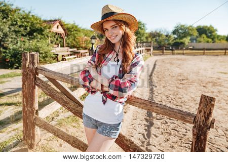 Happy attractive young woman cowgirl standing with hands folded