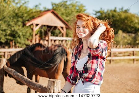 Smiling pretty young woman cowgirl with horse sitting on ranch