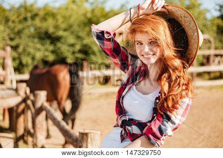 Happy beautiful young woman cowgirl sitting and smiling on ranch