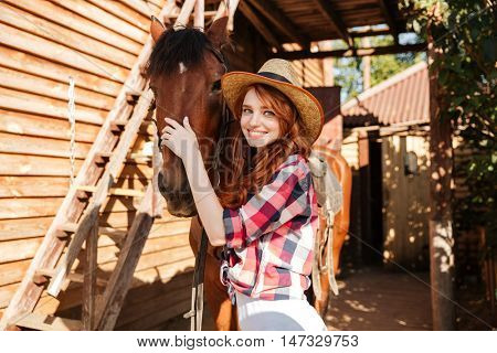Happy attractive young woman cowgirl standing and hugging her horse