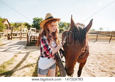 Beautiful redhead young woman cowgirl in hat taking care of her horse on farm