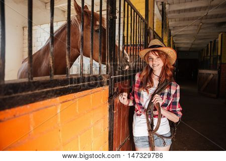 Cheerful attractive young woman cowgirl with horse standing in stable
